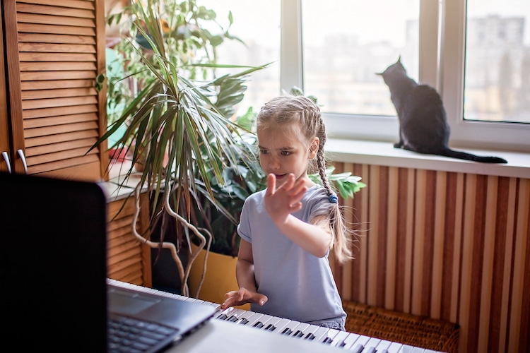 Young piano student learns to play the piano via Zoom