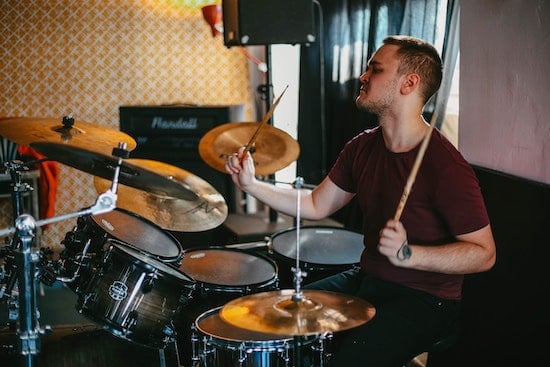 A drum student plays the drums during a lesson.