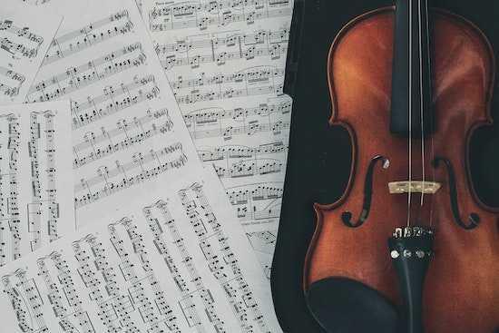A violin and violin sheet music on a table.