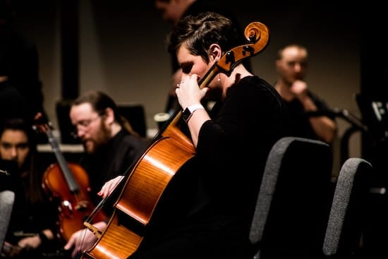 A cellist playing as part of an orchestra.
