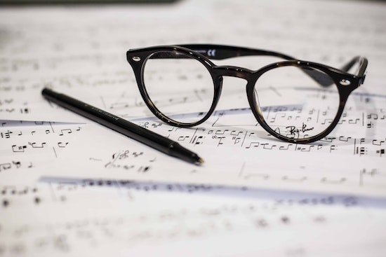 Sheet music with a pen and glasses on it.
