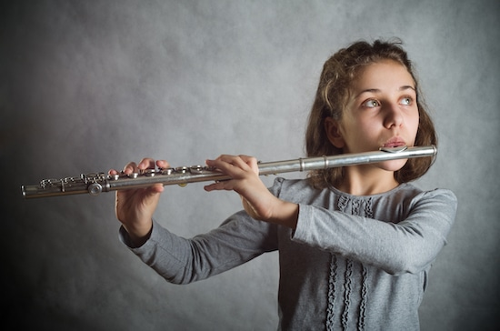A young flutist playing a song.
